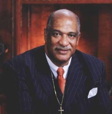 Blog-4-Walter-Kimbrough-red-tie-standing-hands-crossed-cropped
